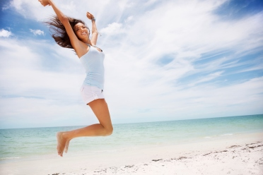 Excited woman jumping with hands raised on beach